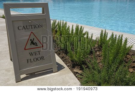 Caution wet floor sign on outdoor swimming pool. Open air poolside with turquoise water and slippery when wet sign.