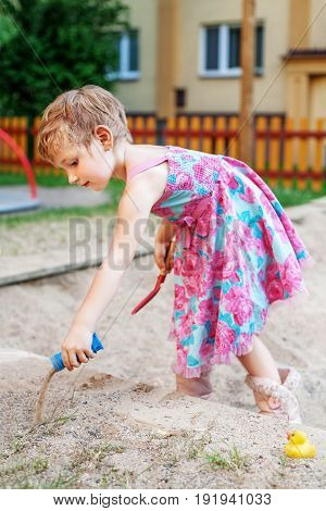 The girl is playing in a sandbox. The concept of lifestyle and childhood.