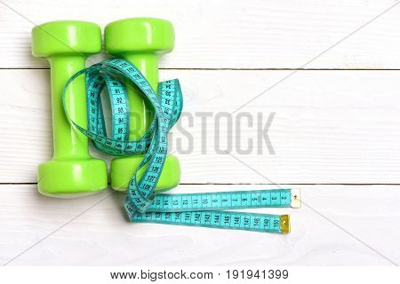 Concept Of Sports And Fitness With Dumbbells And Measuring Tape