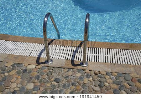 Outdoor swimming pool ladder. Grab bars metal ladder to a blue water open air pool on a sunny day.