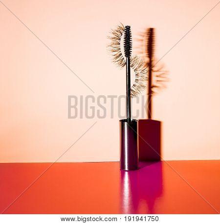 Applicator mascara and false eyelashes with a drop shadow on an orange background