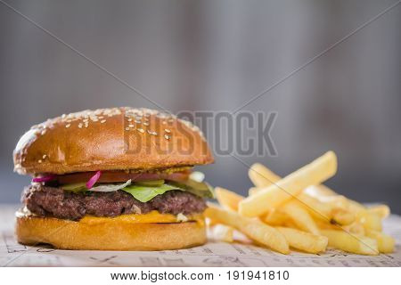 A large tasty burger with potatoes on the table, in a cafe