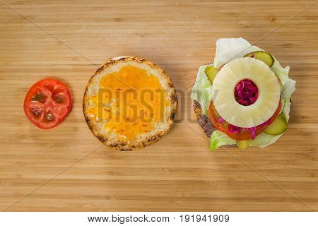 Open burger with pineapple and tomato on the table, top view