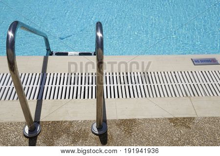 Outdoor swimming pool ladder with no diving sign on poolside. Grab bars metal ladder to a blue water open air pool on a sunny day.