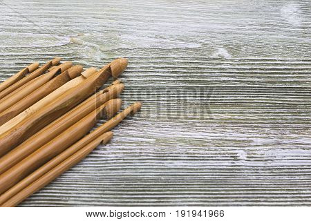 Wooden natural bamboo crochet hooks on the table. Various sizes. Creative work place for homemade crafts. Top view, place for text, copyspace