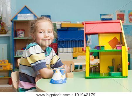Child in kindergarten. Kids in nursery school. Girl playing at infant school. Game