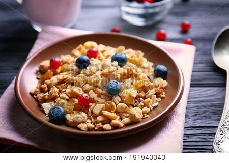 Delicious muesli with berries on wooden table