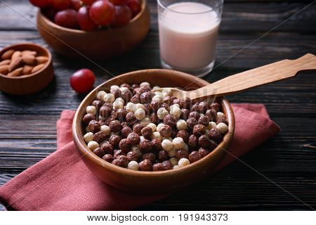 Bowl with delicious cereal balls on wooden table