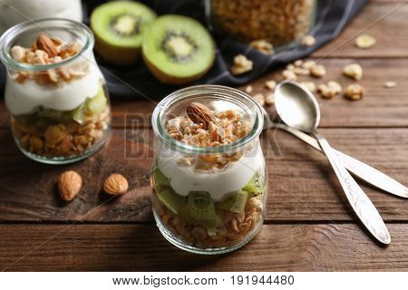 Delicious muesli with kiwi and yogurt on wooden table
