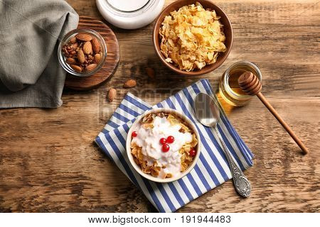 Delicious muesli with berries and yogurt on wooden table
