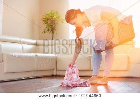 Woman with laundry basket picking clothes from floor in living room