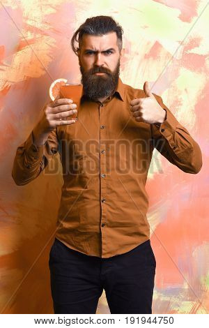 Bearded man long beard. Brutal caucasian serious hipster with moustache in brown shirt holding tropical alcoholic fresh cocktail with orange piece on colorful texture background