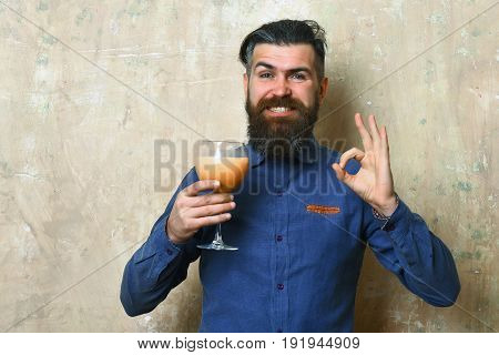 Bearded man long beard. Brutal caucasian smiling happy hipster with moustache in blue denim shirt holding alcoholic fresh cocktail on texture background