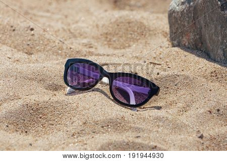 Sunglasses with a dark rim on the sand