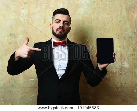 Stylish Man With Satisfied Face And Beard Points At Tablet