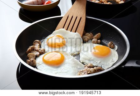 Frying pan with tasty eggs and mushrooms on electric stove
