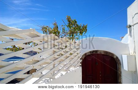 Decorative fence of the white color against the blue sky and bright Burgundy door in Oia on Santorini island