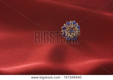 A shiny metal button on a background of red cloth.