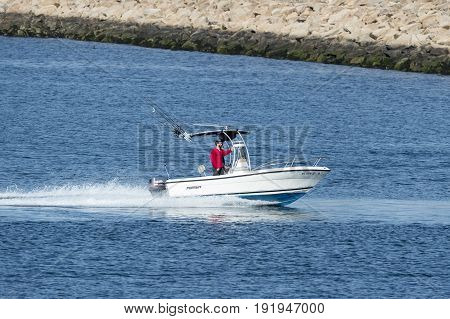 New Bedford Massachusetts USA - May 17 2017: Small powerboat approaching hurricane barrier protecting New Bedford inner harbor