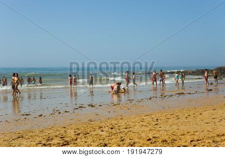 ALBUFEIRA, PORTUGAL - AUGUST 23, 2016: People at the beach of Olhos de Agua in Albufeira. This beach is a part of tourist region of Algarve.