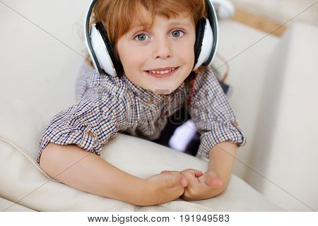 Cute kid. Attractive vibrant imaginative boy sitting on a couch and wearing large headphones while enjoying some nice songs from his playlist