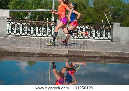 Two Running Girls Are Reflected In The Water