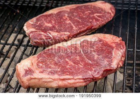 raw barbecue beef sirloin steaks on a grill