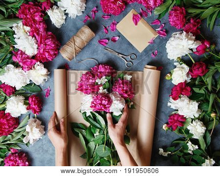 Female florist making beautiful bouquet at flower shop. Florist at work: pretty woman making summer bouquet of peonies on a working gray table. Kraft paper, scissors, envelope on the table.