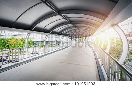 Curved walkway bridge with curved steel roof over road and sunlight.