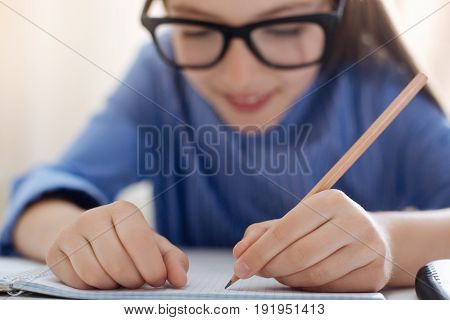 Preciseness in work. Productive incredible responsible lady using a pencil for writing down her homework carefully while completing the assignment