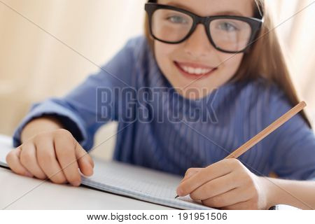 Stunning student. Productive committed vibrant child being a diligent student and working on her assignment while making some notes in her notebook