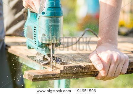 Carpenter saws board with electric jig in park