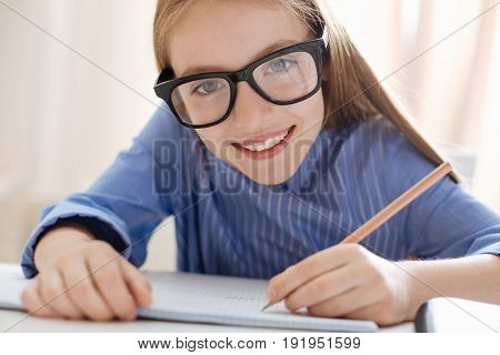 Hardworking and neat. Happy engaging energetic lady sitting at the table and using pencil for writing an essay in her notebook