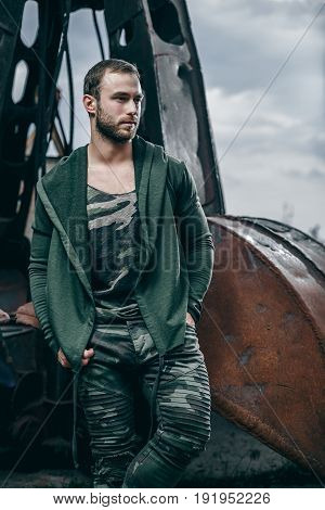 Young handsome fashion bearded model man in urban context. Man in clothes khaki colors on city of urban rusty background.