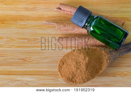 Pure Cinnamon essential concentrate oil extract in green bottle on Cinnamon sticks next to its powder on wooden background with copyspace