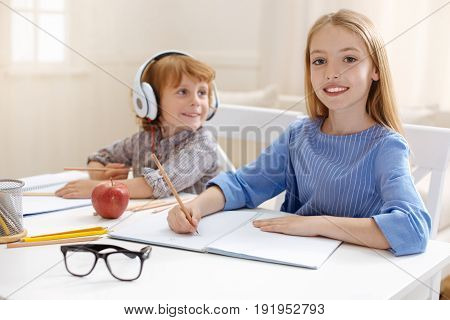 Inspiring kids. Charming logical creative girl sitting at the table with her sibling who also working on his home assignment
