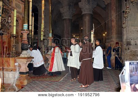 JERUSALEM, ISRAEL - June 15, 2017: franciscans priests during the procession at the entrance to the aedicula of the Holy Sepulchre, old city of Jerusalem, Israel