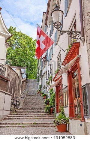 Beautiful view of historic city center of Zurich with Swiss flags at buildings on a sunny day in summer Switzerland