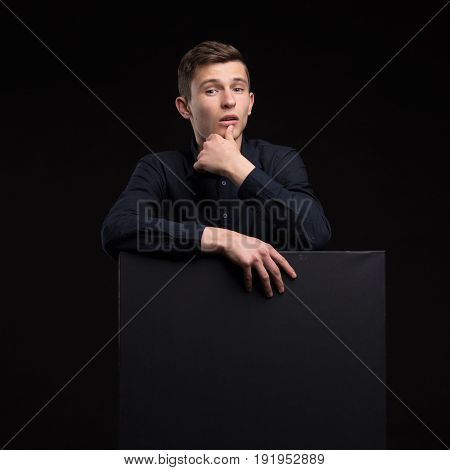 Young interrogative man portrait of a confident businessman showing presentation, paper placard black background. Ideal for banners, registration forms, presentation, landings, presenting concept.