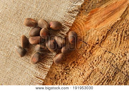 Pine Nuts In A Shuck Closeup On A Napkin From Sackcloth On A Wooden Background.
