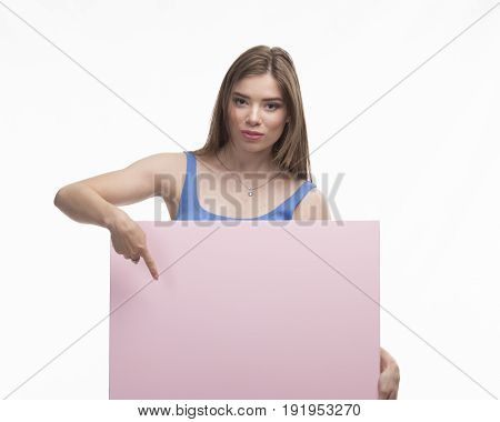 Young happy woman portrait of a confident businesswoman showing presentation, pointing paper placard pink background. Ideal for banners, registration forms, presentation, landings, presenting concept.