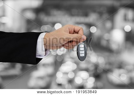 Hand holding car key remote with Bokeh of car traffic background