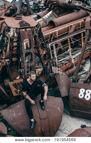 Brutal man with a beard sits on a metal rusty ladle of an abandoned factory. Lifestyle fashion portrait of stylish young man enjoys sunset