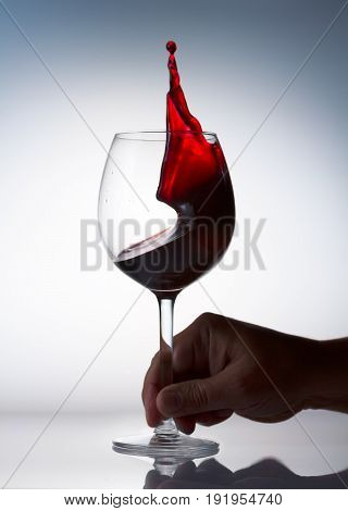 Hand holding glass of red wine with splash