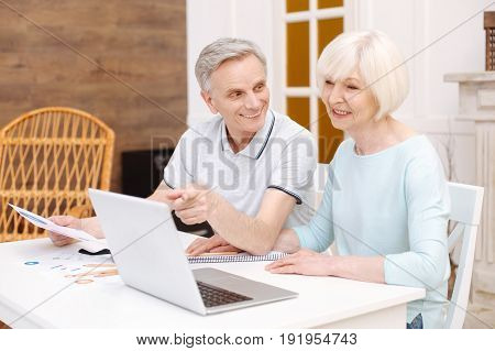 Is that yours. Dedicated talented aged woman sitting at the table and telling her man about the project she working on