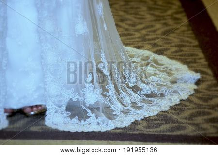 Hem of a white wedding dress Hem of a white wedding dress trailing in the carpet, with the bride's feet showing up
