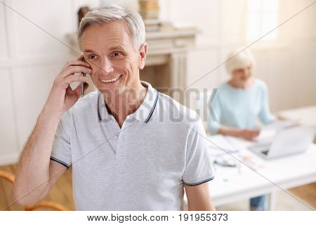 Can we talk now. Nice sincere aged gentleman seeming glad as he talking to an old buddy and sharing some good news with him