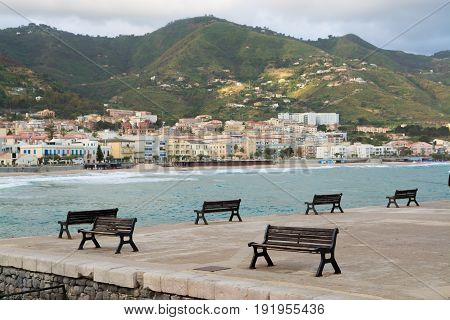 Touristic and vacation pearl of Sicily benches in harbor of small town Cefalu Sicily south Italy