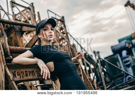 Closeup fashion portrait of hipster young tender woman in black cap and over urban background. Caucasian teen woman model posing indoors.