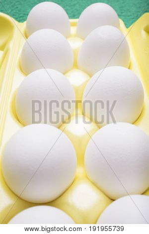 Ten white chicken eggs lie in a yellow tray a vertical frame